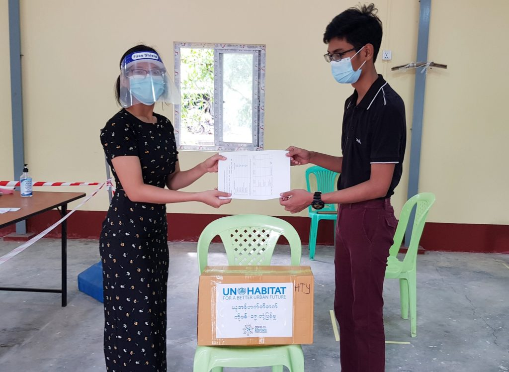 UN-Habitat Staff member hands over the PPE to a representative from the Hlaingthayar fever clinic. Photo by UN-Habitat.