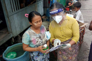 A community volunteer explains the contents of the IEC pamphlets to a community member in Hlaing Tharyar. Photo by Bedar Social Development Group